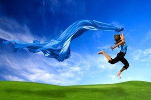 Junge Frau mit blauem Schal springt über Wiese