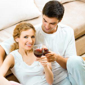 Paar trinkt Rotwein im Wohnzimmer