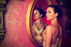 Schöne Frau im Kleid steht vor Spiegel