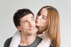 Frau küsst Mann auf Wange