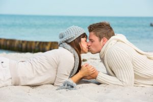 Küssendes Paar liegt im Sand