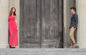 Junges Paar steht vor großer Holztüre