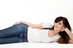 Liegende Frau mit Jeans und weissem T-Shirt