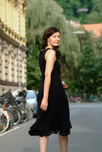 Frau im schwarzen Kleid blickt sich um