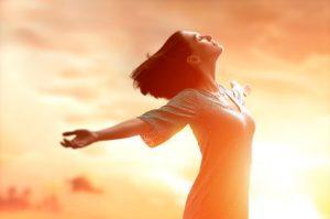 Frau streckt sich im Sonnenaufgang