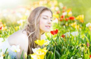 Junge Frau mit geschlossenen Augen liegt in Blumenwiese