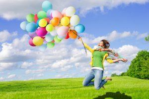 Frau mit bunten Ballons auf Sommerwiese