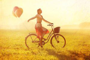 Frau mit Fahrrad im Sommer