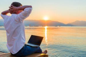 Mann sitzt mit Laptop auf Steg am See