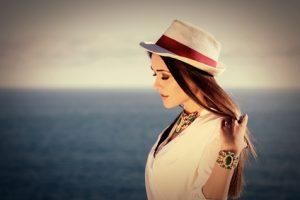 Schöne Frau mit Hut am Meer