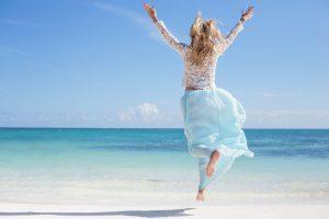 Frau macht Freudensprünge am Strand
