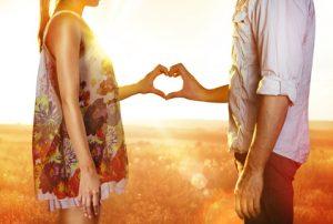 Paar formt ein gemeinsames Herz mit den Händen